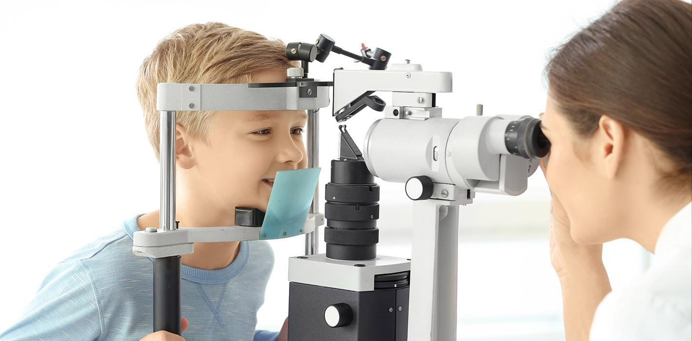 young boy having eyes checked through slit lamp